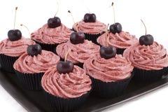 Queques do chocolate, com geada vermelha e uma cereja Foto de Stock Royalty Free