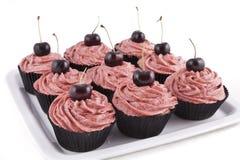 Queques do chocolate, com geada vermelha e uma cereja Imagem de Stock