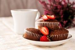 Queques do chocolate com morangos em uns pires com uma xícara de café branca fotos de stock royalty free