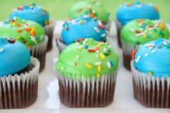Queques do chocolate e geada colorida Imagem de Stock Royalty Free