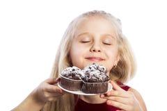 Queques do chocolate sniffing da menina Imagens de Stock Royalty Free