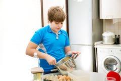 Queques do cozimento da criança do menino Escolar da criança que prepara queques na cozinha Fotos de Stock