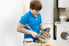 Queques do cozimento da criança do menino Escolar da criança que prepara queques na cozinha Fotografia de Stock