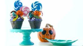 Queques do estilo do bolo do gotejamento do candyland de Dia das Bruxas com pirulitos e doces no branco vídeos de arquivo