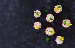 Queques do limão com creme da cereja Arando, folhas de hortelã Alimento em um fundo escuro Vista superior Imagem de Stock