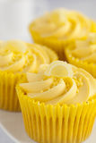 Queques do limão com redemoinho do creme da manteiga e a decoração cândido do fruto Fotografia de Stock Royalty Free