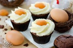 Queques do ovo da páscoa - queques do chocolate com geada do queijo creme Imagem de Stock