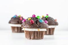 Queques engraçados do chocolate decorados com os doces coloridos no fundo branco Fotografia de Stock Royalty Free