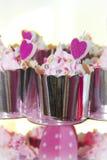 queques festivos em um pacote brilhante com a decoração sob a forma dos corações de creme e cor-de-rosa imagens de stock royalty free