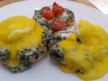 Queques ingleses do café da manhã cobertos em ovos escalfados dos espinafres e no molho desnatados do hollandaise Foto de Stock Royalty Free