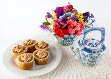 Queques no doily com flores Imagem de Stock
