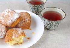 Queques razoavelmente saborosos e dois copos do chá Fotos de Stock Royalty Free