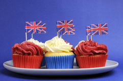 Queques vermelhos, brancos e azuis do tema inglês com as bandeiras de Grâ Bretanha Union Jack foto de stock royalty free