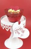 Queques vermelhos de veludo com geada da baunilha e corações vermelhos bonitos no suporte Fotografia de Stock