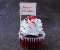 Queques vermelhos festivos de veludo com um cartão do cumprimento Imagens de Stock Royalty Free