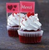 Queques vermelhos festivos de veludo com um cartão do cumprimento Fotos de Stock Royalty Free