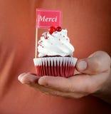 Queques vermelhos festivos de veludo com um cartão do cumprimento Fotografia de Stock Royalty Free