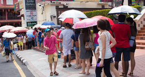 Quequing on a sunny day. In a long queue people waiting side of the road Royalty Free Stock Image