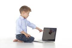 a criança indica o portátil Fotografia de Stock