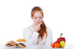 Querendo saber se comer doces ou vegetais Imagens de Stock