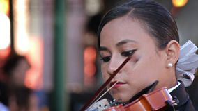 Mariachi woman playing a violin in the public square. QUERETARO, MEXICO 2016 (ILLUSTRATIVE IMAGE). Mariachi woman playing a violin in the public square. The stock video footage