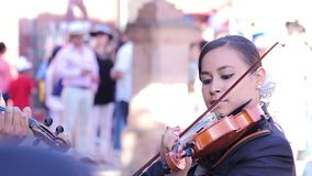 Mariachi woman playing a violin in the public square.