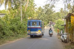 Blue indian bus and motorbike on a village street stock photo