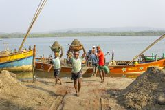 Bowls with sand on their heads, Indian men unload a boat with sand against the background of a. Querim, Goa/India - 22.01.2019: Bowls with sand on their heads stock photos