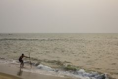 Indian fisherman with a fishing net on a sandy beach against the ocean in the evening royalty free stock image
