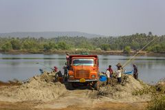 Indian men load sand into a red truck on the background of a blue boat in the river and green palm. Querim, Goa/India - 10.01.2019: Indian men load sand into a stock photography