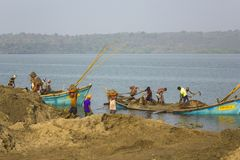 Indian men unload sand from boats against the background of the river and green forest. extraction. Querim, Goa/India - 22.01.2019: Indian men unload sand from royalty free stock photos