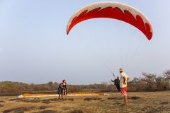 Preparation for take-off tandem paraglider on the background of dry savanna and a landing man on a. Querim, Goa/India - 19.01.2019: Preparation for take-off stock photography