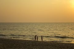 three dark silhouettes of children on the yellow sand of the beach against the sea and the evening stock photo