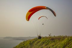A tandem of paragliders on a yellow red parachute flying over the sea and a green hill on the royalty free stock photos