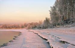 Querneigung des Flusses, abgedeckt mit Schnee und hellen Bedingungen, die untergehende Sonne lizenzfreies stockbild