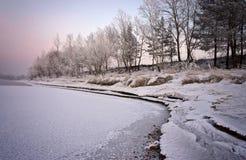 Querneigung des Flusses, abgedeckt mit Schnee und hellen Bedingungen, die untergehende Sonne stockfoto