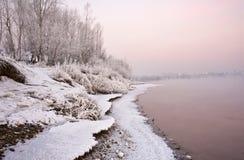 Querneigung des Flusses, abgedeckt mit Schnee und hellen Bedingungen, die untergehende Sonne lizenzfreie stockfotos