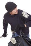 Querneigungräuber, der mit Geld läuft Stockfoto