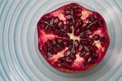 Querschnitt des Granatapfels auf blauer gestreifter Platte stockfoto