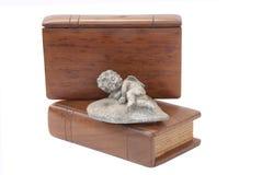 Querube encima de dos biblias cubiertas de madera Fotografía de archivo