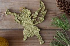 Querube y ramas de árbol de navidad de oro Foto de archivo libre de regalías