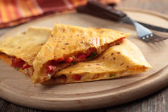 Quesadilla. Wedges of quesadilla on a round cutting board royalty free stock images