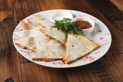 Quesadilla with chicken. Quesadilla with beef and chicken on brown wood table. quesadilla and sauce Stock Image