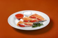 Quesadilla with chicken and tomatoes, two sauce. S from tomatoes and sour cream. It is decorated with parsley. On a monophonic background. Side view Stock Photo