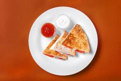 Quesadilla with chicken and tomatoes, two sauce. S from tomatoes and sour cream. On a monophonic orange background. Side view Stock Image
