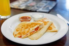 Quesadilla with chicken and tomatoes, two sauce. S from tomatoes and sour cream. Low key. Side view Stock Photo