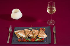 Quesadilla filled with vegetables, a glass of white wine. On the plateau royalty free stock photos