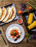 Quesadilla, salad with cottage cheese and tomatoes, two corn on wood table. Top wiev. Fresh dinner Royalty Free Stock Image