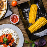 Quesadilla, salad with cottage cheese and tomatoes, two corn on wood table. Top wiev. Fresh dinner Royalty Free Stock Images