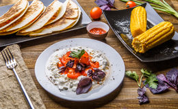 Quesadilla, salad with cottage cheese and tomatoes, two corn on wood table. Top wiev. Fresh dinner Stock Image